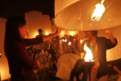 Holding down the lantern so they can fill with hot air during Loy Krathong in Chiang Mai, Thailand