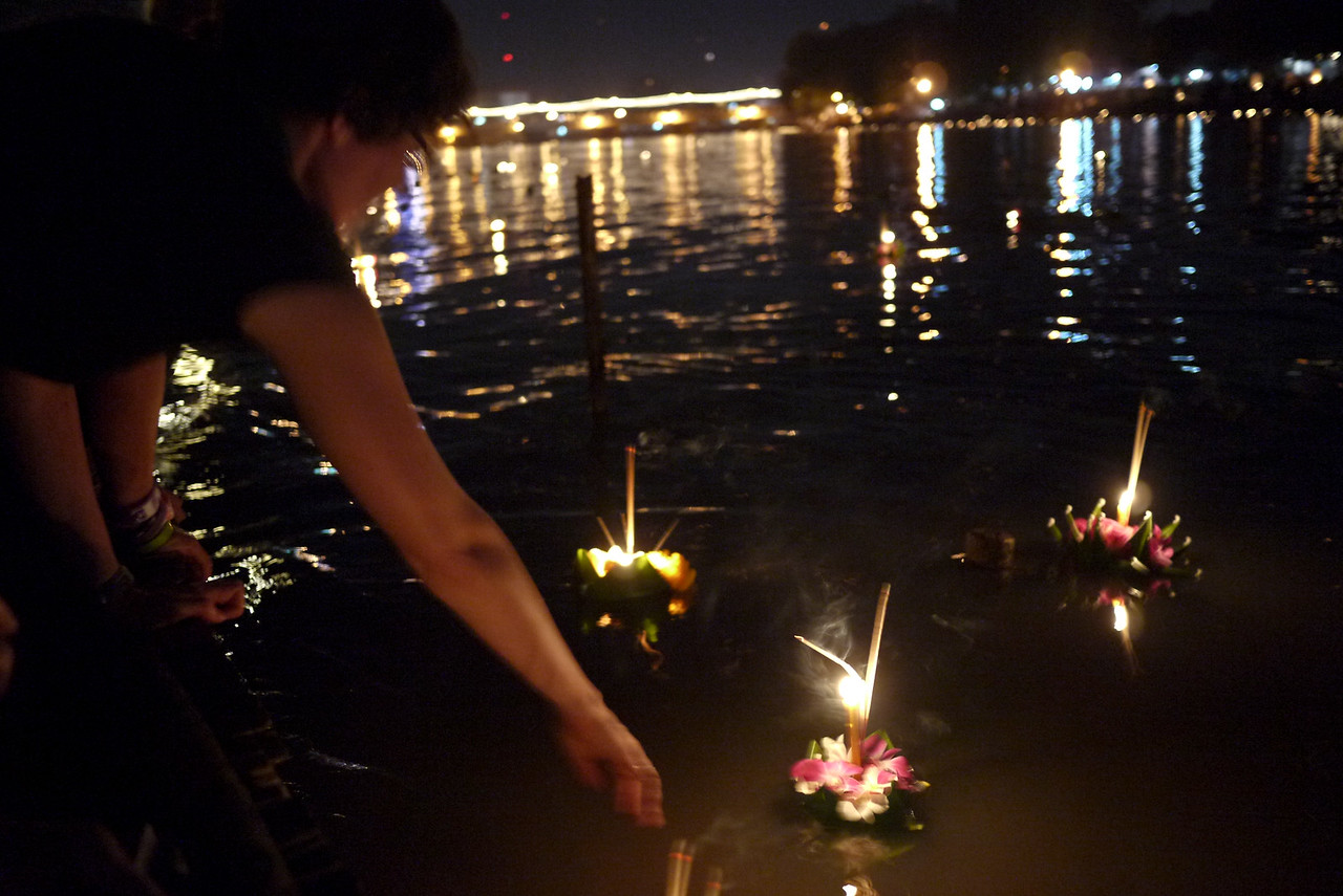 Splashing the water to encourage the krathongs to leave the shoreline during Loy Krathong in Chiang Mai, Thailand