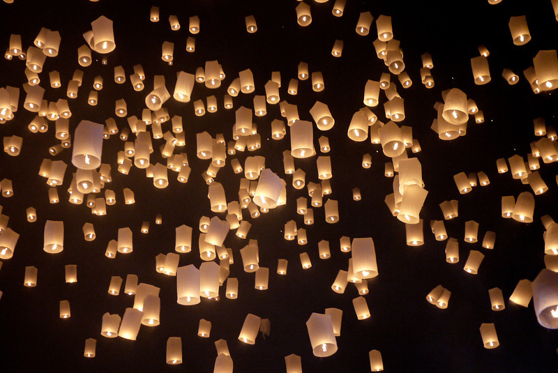 A wave of lanterns swiftly float into the air during Loy Krathong in Chiang Mai, Thailand
