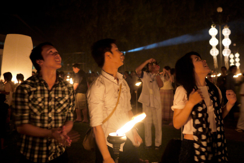 Wonder and hope on their faces as their lantern takes flight during Loy Krathong in Chiang Mai, Thailand