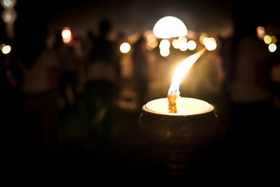 A candle flame dances in the wind as we prepare for lighting the lanterns during Loy Krathong in Chiang Mai, Thailand