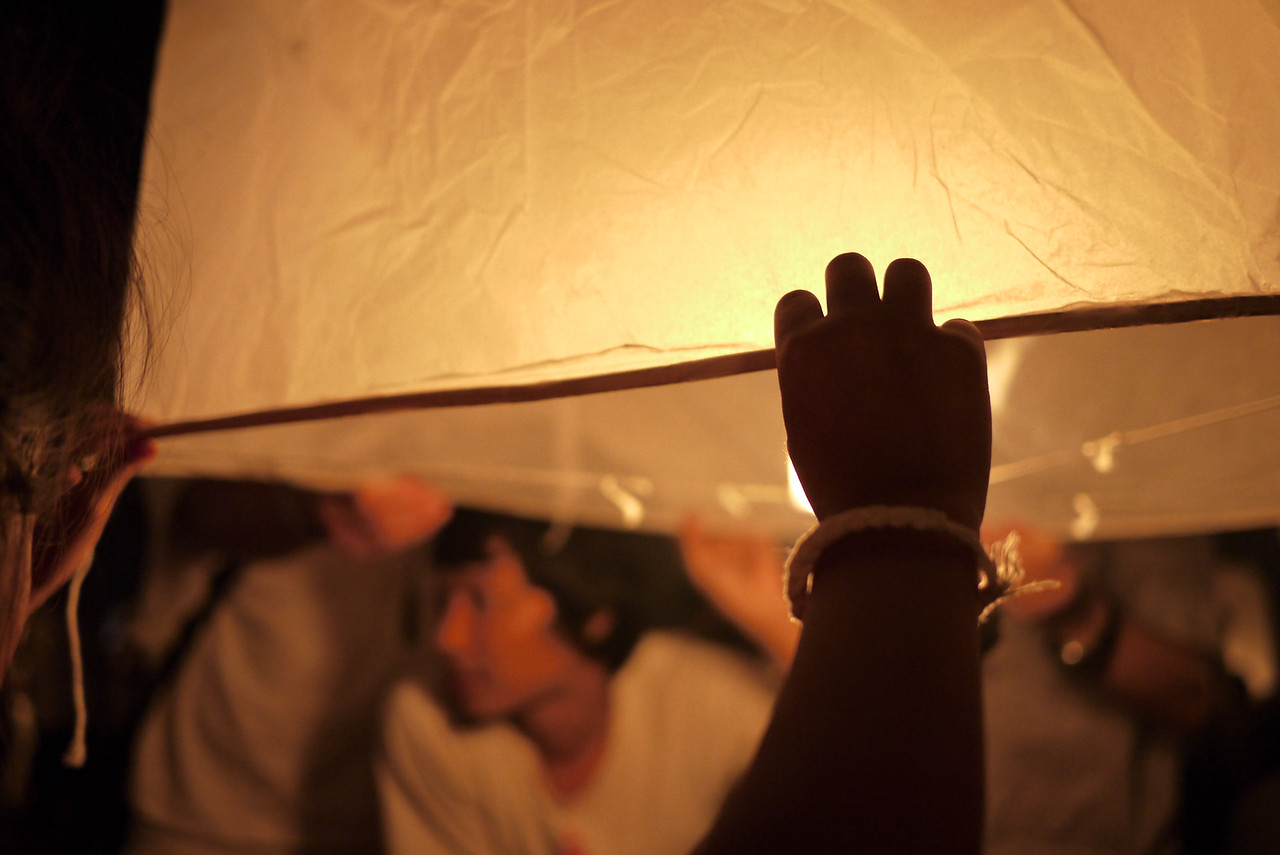 A tiny hand helps hold down the lantern during Loy Krathong in Chiang Mai, Thailand