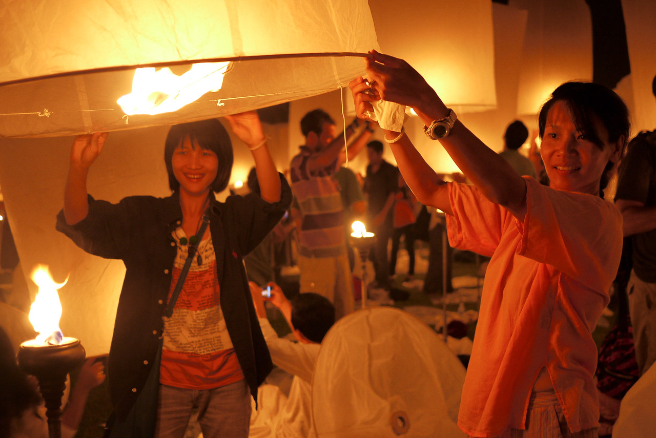 A and Jenny prepare the lantern for release during Loy Krathong in Chiang Mai, Thailand