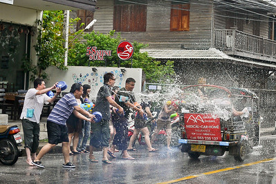 Nailing a passing tuk-tuk with water bucketsSongkran in Chiang Mai, Thailand.