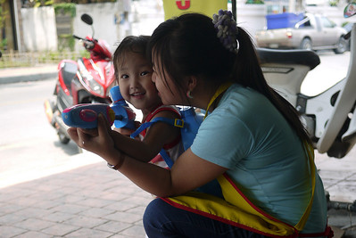 Mom and daughter lie in wait of innocent pedestrians! Songkran in Chiang Mai, Thailand.