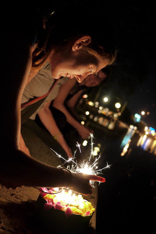 Lighting the sparklers and incense during Loy Krathong in Chiang Mai, Thailand