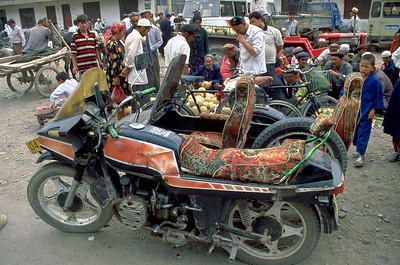 Upholstered motorbike on the bazar in Kashgar 1999,  Epic travel with my friend Arthur along eastern Silk Road in 1999. Kashgar, an oasis city in Xinjiang, China on the foot both of Pamirs and Tian Shan Mountains. Located near the border with Kyrgyzstan, Tajikistan, Afghanistan, and Pakistan Kashgar has a rich history as a trading post and melting pot. Back in 1999 it was busy, ethnic, uyghuric and a highlight of our journey. Wonder what it's like today.