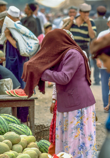 Veiled woman choosing melons on the market of Kashgar, Xinjiang Uygur Autonomous Region, China