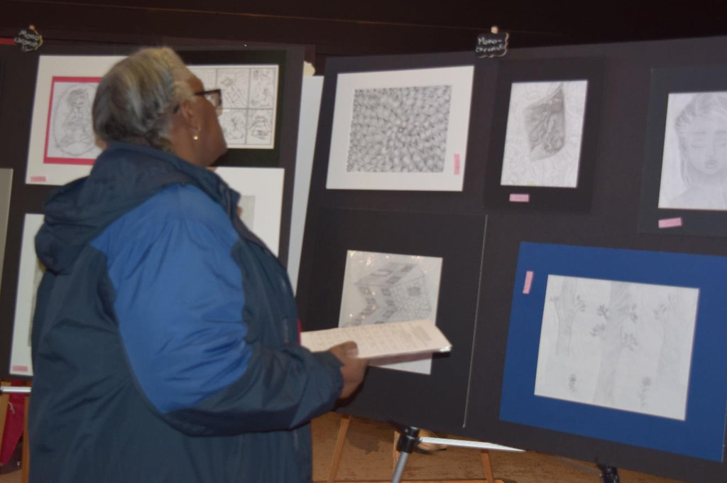 . Veronica Holmes, one of the 21 official judges at Saturday night�s art competition, studies the pen and ink drawing.