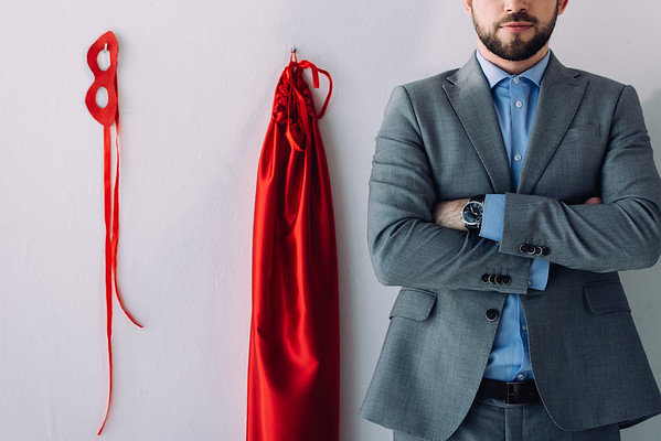 cropped image of super businessman standing with crossed arms near mask and cape on wall in office