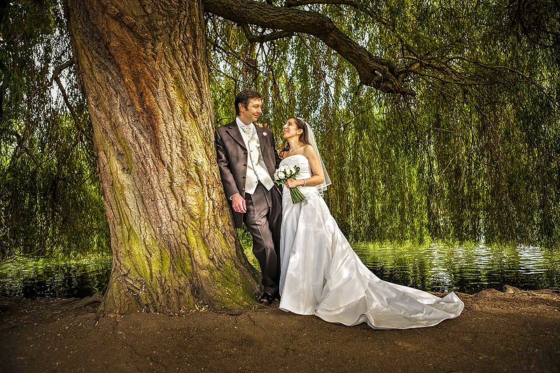 bride and groom leaning against tree