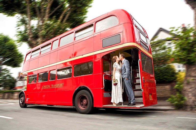 bride and groom kissing on a wedding bus