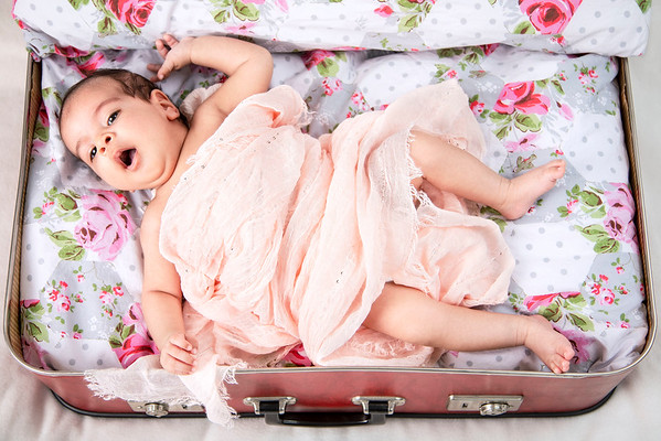 new born baby girl yawning wrapped in a pink blanket in an open suitcase