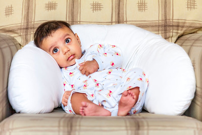 baby boy resting against a pillow in an armchair