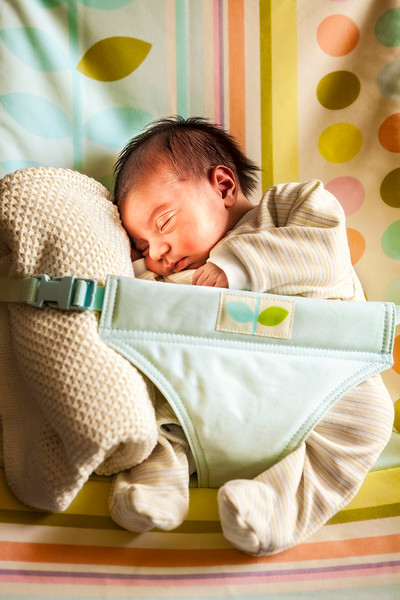 new born baby boy sleeping secured to a rocking seat