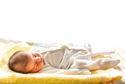 new born baby boy sleeping on a yellow blanket
