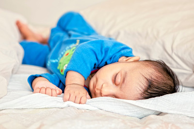baby boy sleeping on a bed in blue pyjamas