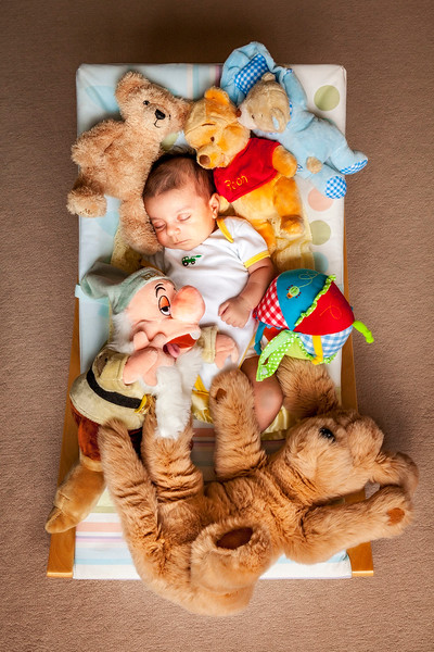 new born baby boy sleeping in a rocking seat surrounded by cuddly toys