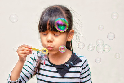 girl blowing bubbles with her eyes closed