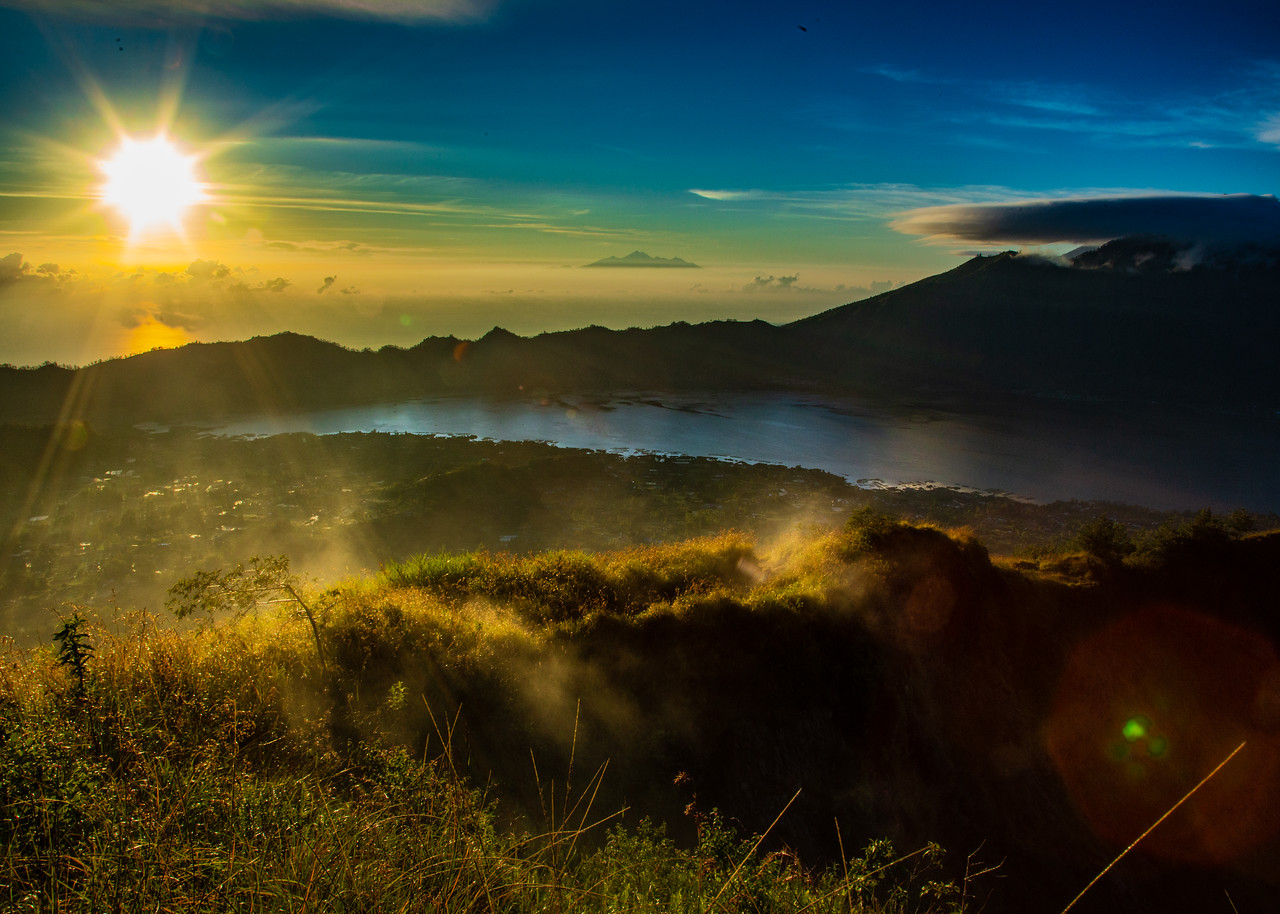 Sunrise from Mount Batur Volcano. On the right in Mount Agung. Just below the sun, you can see a reflection off of the Bali Sea. In the middle, on the horizon, is the island of Lombok. Steam is from volcanic vents. Lake Batur and Songkan are at the bottom of the caldera.