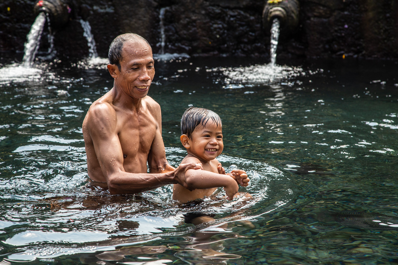 Grandfather teaching his Grandson to Swim at Family Bathing at Holy Spring in Bali