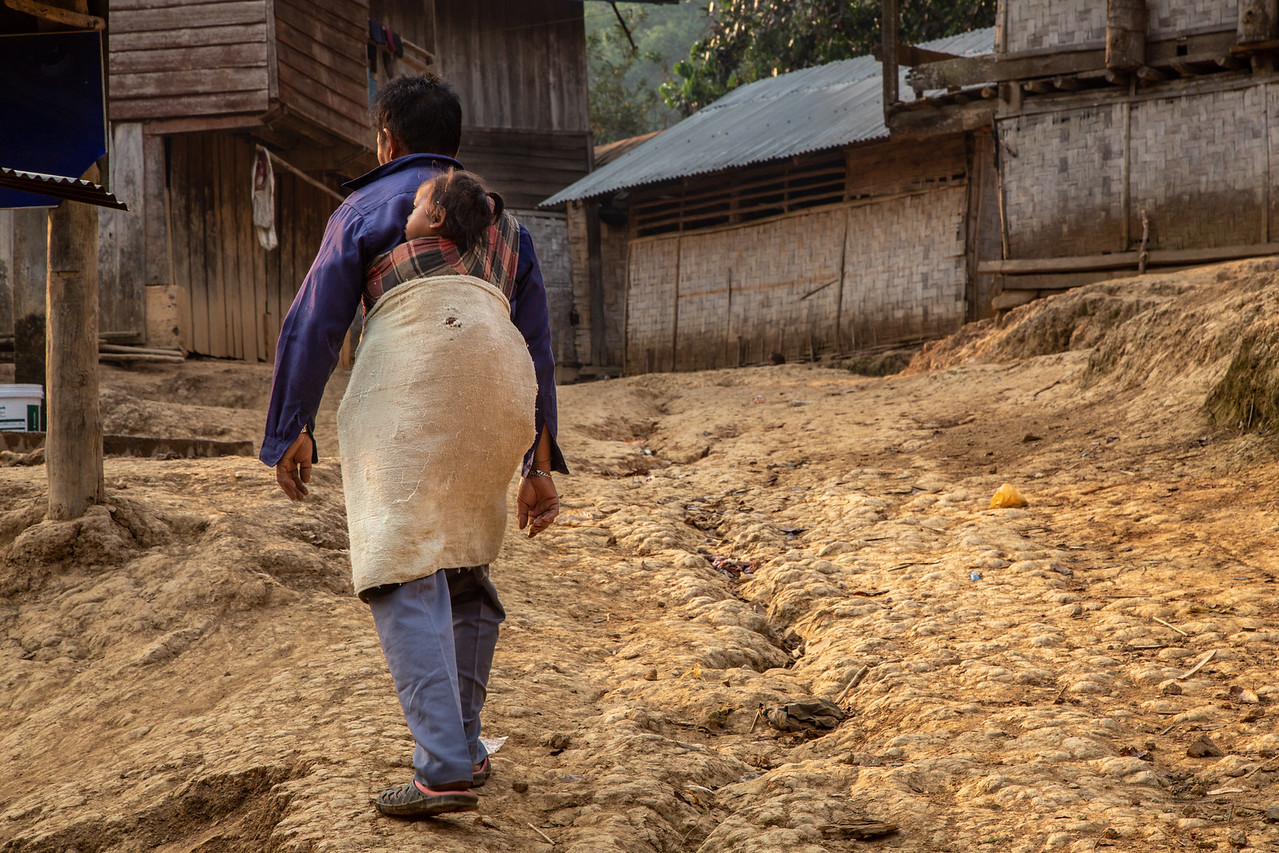 Grandfather Caring for His Granddaughter in a Laotian Hill Tribe Village