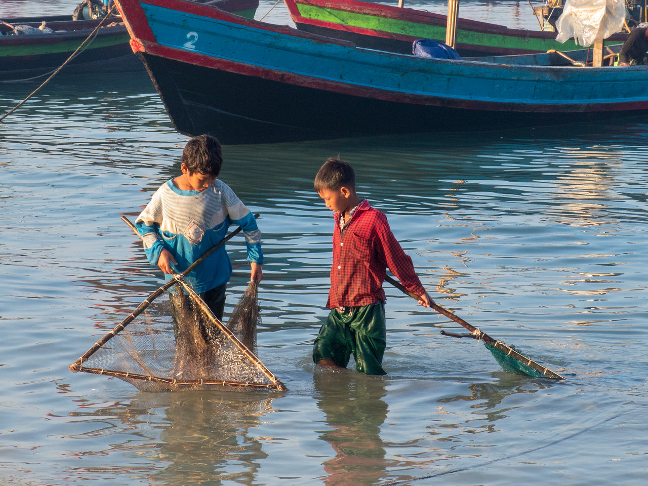 Nothing is Wasted. The Boys are Netting Spillage from the Fishing Boats