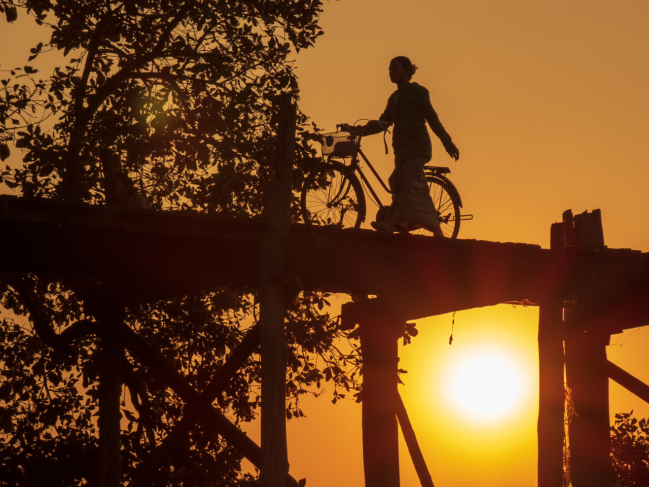 Silhouette of a Woman Crossing the Ubine Bridge on Bicycle
