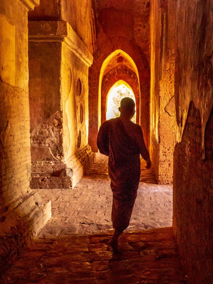 A Saffron Robed Monk Walks Through a Temple of Bagan
