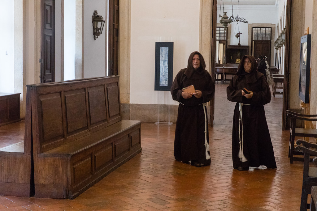 Volunteer monks wandering the corridors of Mafra Palace