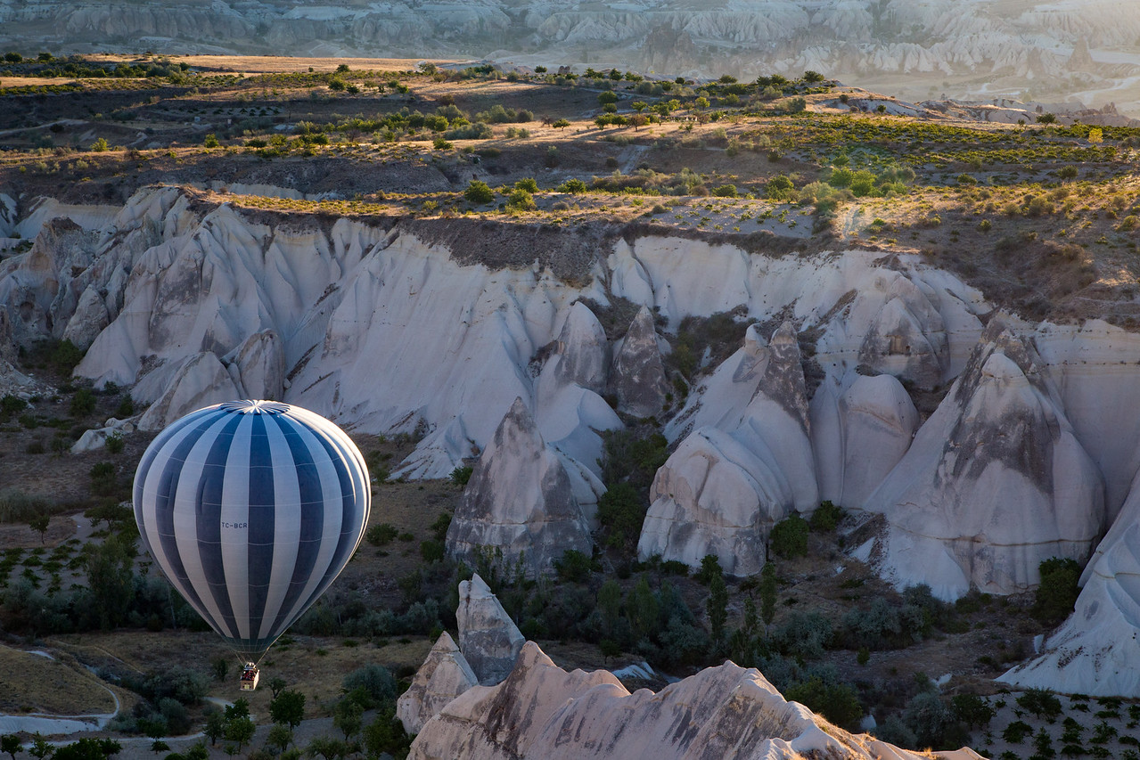 Hot air balloon maneuvering among the fairy chimneys in Cappadocia, Turkey