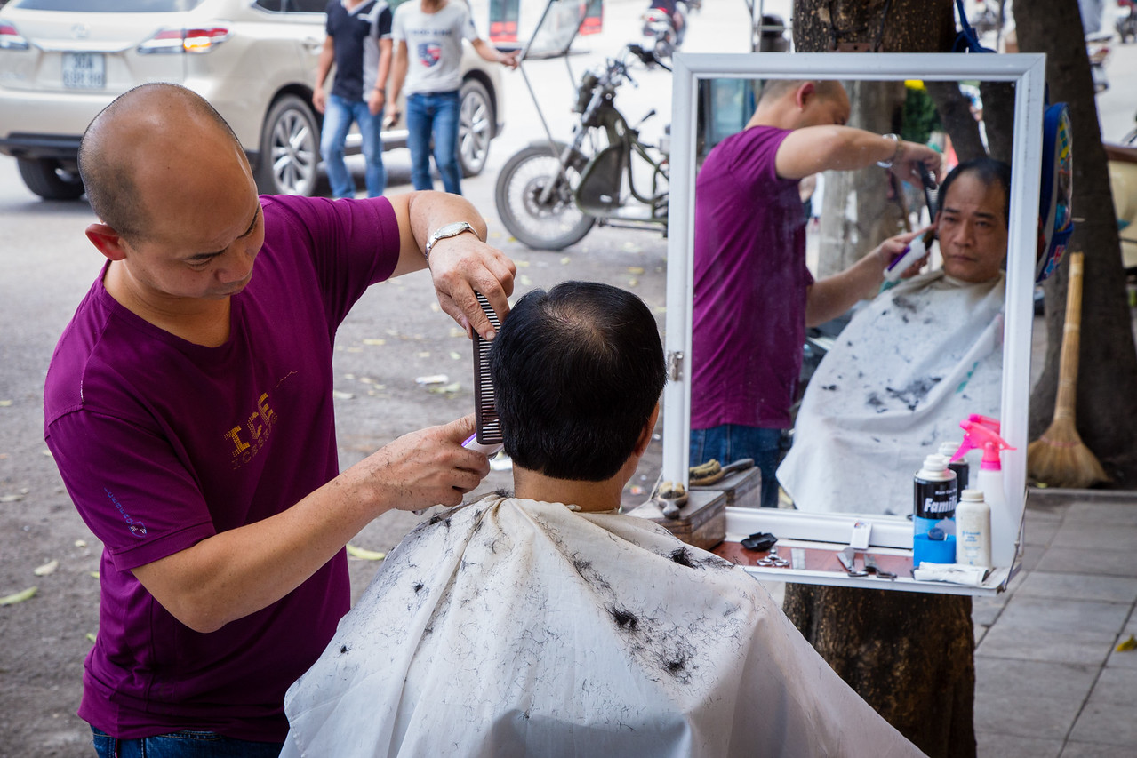 Barber Giving Haircut on the Streets of Vietnam