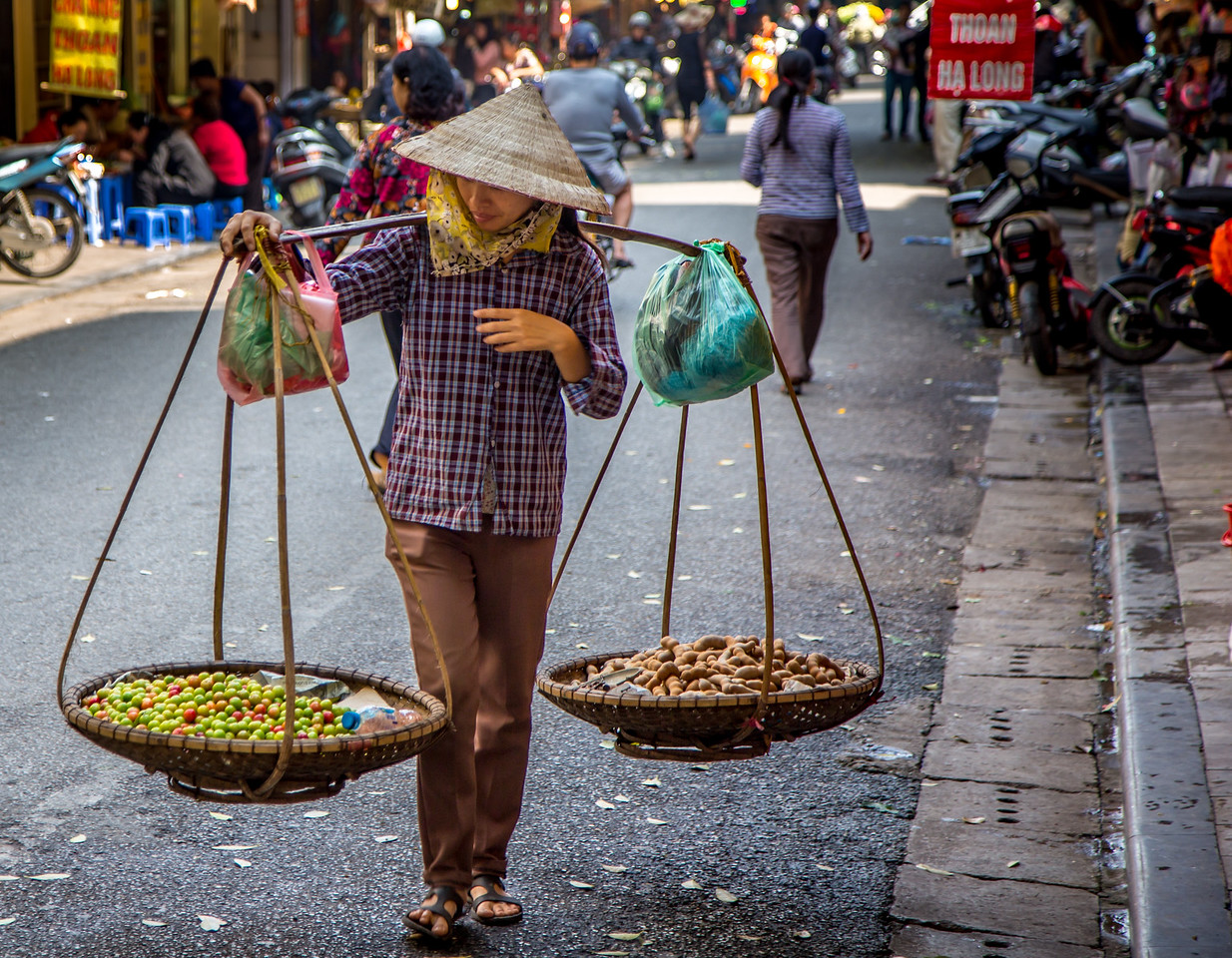 Woman Selling Produce Uses a Carry Pole
