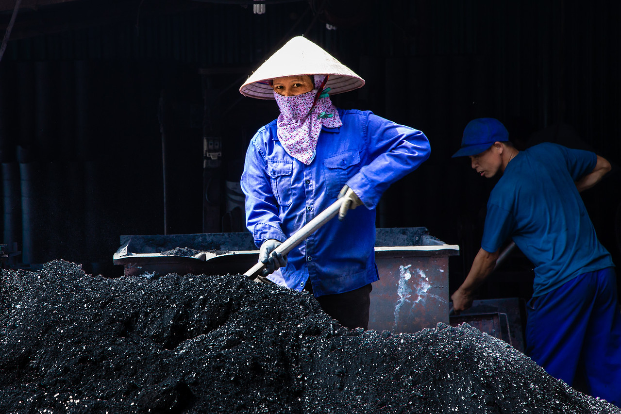 A Woman Shovels Charcoal to Compress for Use in Stoves