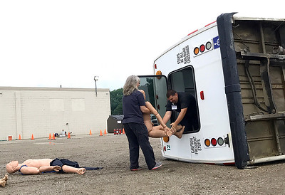 """Lisa Yanick Litwiller  Morning Sun  In this bus accident training drill, ICTC drivers Ryan Roderick and Jean Bollinger work to pull """"victims"""" from an overturned public transit bus, part of the drill help at Green's Towing in Mt. Pleasant on Saturday, July 22, 2017."""