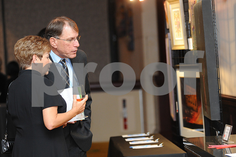 CAMPFIRE GALA 2013<br /> DEBBIE AND BRAD HEATH  look over some of the artwork that is up for auction.
