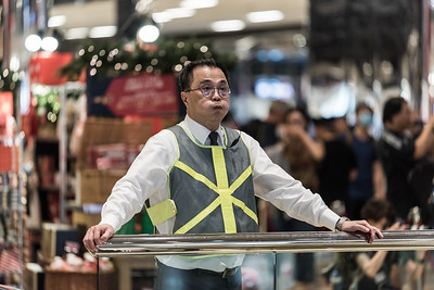 A mall security guard looks on as hundreds of local residents gather inside the CityPlaza Mall in Taikoo Shing, Hong Kong to sing and hold hands in solidarity. Families with kids, seniors with flip phones, and passionate youth gathered peacefully in protest against what they view as an authoritarian government and an unaccountable police force. November 3, 2019.