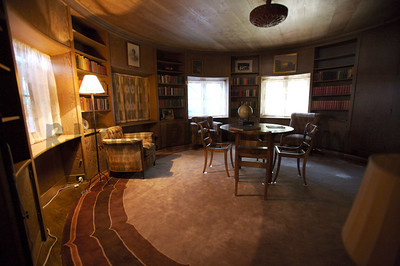 1st floor library in the turret.  Features a circular carpet, wooden ceiling, and fireplace for cozy evenings with guests. The Chinese cashmere rug was acquired for $40k.