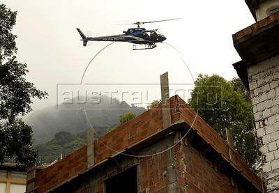Military policemen in an helicopter patrol at the Rocinha shantytown, Rio de Janeiro, Brazil, November 13, 2011. (Austral Foto/Renzo Gostoli)