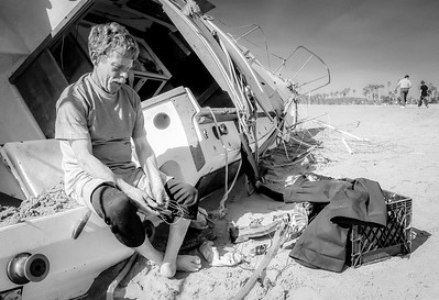 55 Year old Jeff Catlin sits in the ruin of his sailboat after it washed ashore in a storm. Catlin lost his foot in a construction accident.