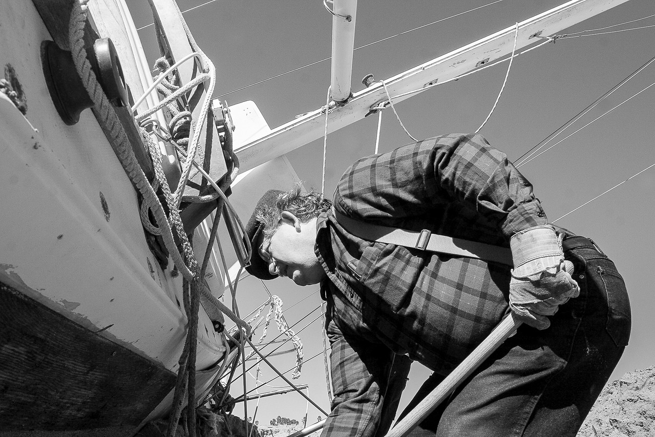Architect Tom Smith digs beneath a storm stranded sailboat in an effort to help the owner salvage his home after hearing about the man's plight on the Santa Barbara evening news.