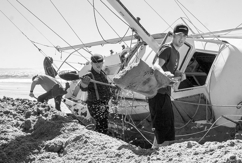 Volunteers Josh Luft a Marine Electrician, Tom Smith an Architect and Chris Benton a retired firefighter (R-L) help dig out a storm stranded sailboat from Santa Barbara's East Beach.
