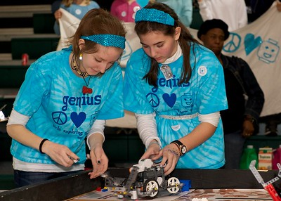Before each task, the girls exchange sensors and attachments to customize the robot for its next task