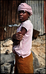 A young girl watches with wary eyes while her destroyed school is being torn down and rebuilt in the Turgeau neighborhood of Port-au-Prince. The 7.0 force earthquake killed more than 200,000 people and left over a half-million without shelter.