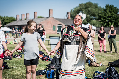 Kim Wheatley and the Red Spirit Singers Drum Group lead a group of school children in a traditional dance at the opening of the Indigenous Arts Festival at Fort York in Toronto. June 21, 2018.