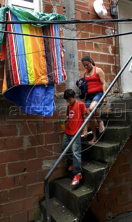CLUBINHO DA CRIANCA-PLANETARIO -   Carlos Henrique Pereira de Souza e Agda, sua mae, saindo da sua casa na favela Santa Marta,  Rio de Janeiro, Brasil, Novembro 26, 2011.  (Austral Foto/Renzo Gostoli)