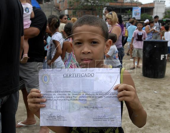 DIA DAS CRIANCAS NO ALEMAO - O menino Ranniel Brum de Lima mostra o diploma que ganho num concurso escolar durante a festa no Complexo do Alemao, Rio de Janeiro, Brasil, Outubro 12, 2011.  (Austral Foto/Renzo Gostoli)