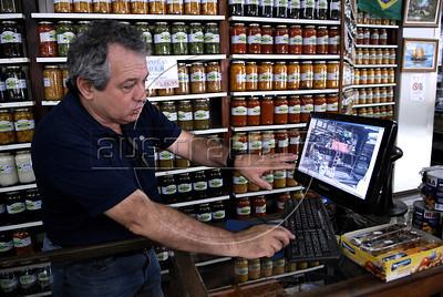 NOVA FRIBURGO UM ANO DEPOIS -  Gilberto Sader, dono de loja na Praca do Suspiro, Nova Friburgo, mostra fotos dos danos da inundacao, Rio de Janeiro, Brazil, Janeiro 26, 2012. (Austral Foto/Renzo Gostoli)