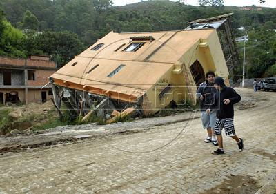 NOVA FRIBURGO UM ANO DEPOIS - Jovens passam frente a casas de Nova Friburgo danificadas pelos deslicamentos e chuvas de 2011, Rio de Janeiro, Brazil, Janeiro 26, 2012. (Austral Foto/Renzo Gostoli)