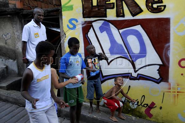 """Otavio Cesar Junior """"O livreiro do Alemao"""", fundador do projeto """"Ler  é Dez – Viva Favela!""""com criancas do projeto, no Complexo do Alemao, Rio de Janeiro, Brazil, junho 24, 2011. (Austral Foto/Renzo Gostoli)"""